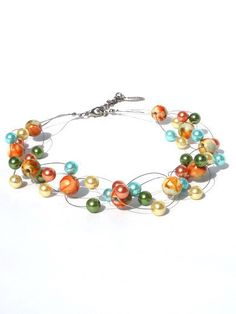 This necklace is made of glass pearls and multi-coloured beads. The glass pearls are in the colours aquamarine, gold, orange and army green.    Length