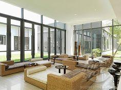 SuperStock - Wicker furniture in large modern sunroom