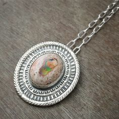 This necklace features a beautiful Mexican opal. This opal has beautiful flashes of red and green. This setting was hand made from solid sterling silver, and hand stamped with a repetitive rhythmic pattern. This has been patinad. You choose the length of the chain. Opal measures: 14mm x 17mm Pendant measures: 30mm x 32mm
