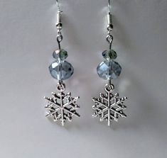 This is a pair of silver tone Snowflake drop earrings with pale blue rondelle crystals. They dangle 1.5 inches long from their silver plated hook. These earrings are perfect for the Winter holidays or even for a Christmas in July