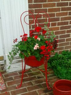 Bought this antique ice cream parlor chair for $16 and can of red Rust-Oleum high-gloss spray paint for $4.  The paint was chipping off and it was missing the seat.  Put some flowers in an antique firemans bucket that was already red.  What fun!