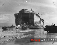 World War II Photograph: At Bititu Island, Tarawa atoll, trucks run supplies from the belly of a Coast Guard-manned LST across protecting reefs that guarded the heavily-fortified island.  Five hundred yards of reef girded the shore, according to Coast Guard Lieutenant R.T. Leary of Green Farms, Conn., who commanded this LST.