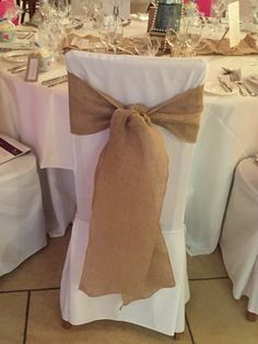 Hessain sash on chair covers at Rivervale Barn. Perfect for a country / rustic style wedding by Fuschia.