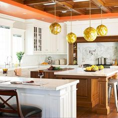 love the giant island stained to be in contrast with all the white, multiple stool locations, layout, and height of the windows in a stack with crown. the coffered ceiling sets the whole thing off with the splash of orange and geometric globes. wow - this is a great kitchen <3