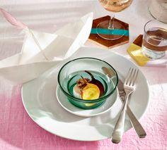 Na stole je prestretá miska, malý tanierik a tanier usporiadané na sebe s loďkou z papiera naboku.