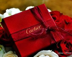 Cartier jewelry box, wrapped with a red bow.