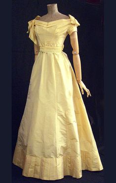 Ball Gown: ca. 1870, iridescent taffeta, hand-sewn polished cotton-lined bodice with wide neckline and shoulder bows, skirt longer and fuller in back with inner cord, pleated bustle pad and pleated hem flounce, sash of matching moiré  ribbon with scalloped satin edges.