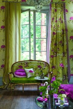Greens and purples in bold patterns across drapes and love seat not sure if I love or hate this