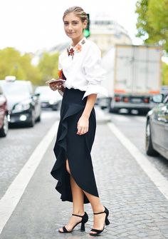 Jenny Walton wears an embellished button-down shirt, high-slit skirt, and sandals