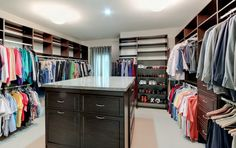 A spacious walk-in closet with island and custom organization system. Designed and built by Ramage Company.