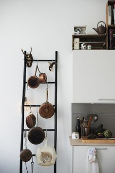 Use a ladder to hang pots. This way the pots won't scratch the wall but you would want to insure that the ladder was firmly placed and that it had some form of wall protection.