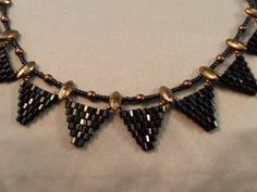Free step by step directions for how to make the Gotham City Necklace, designed by Jennifer VanBenschoten, using brick stitch triangles made from size 8 Delica beads and vintage marquis shaped 2-hole nailheads.
