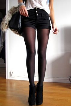 Sheer black tights and black shorts, and black suede bootie heels