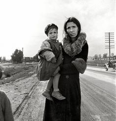 """February 1939. """"On U.S. 99 near Brawley, Imperial County, California. Homeless mother and youngest child of seven walking the highway from Phoenix, Arizona, where they picked cotton. Bound for San Diego, where the father hopes to get on relief 'because he once lived there.'"""" Medium-format nitrate negative by Dorothea Lange for the Farm Security Administration."""