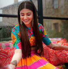 A graphic-print Sabyasachi lehenga in fuchsia pink and Indian orange for Anushka Sharma's mehendi