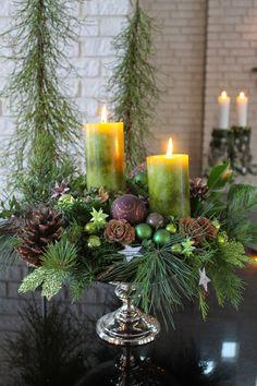 Kerststuk met o.a. kerstgroen, dennenappels, kerstballetjes en kaarsen