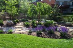 I love this picture of a section of this yard. My favorite element is how the plants and trees are planned out so well. I think that is an important part of landscaping. The structure of your yard is important, but you also have to decide what you are going to do with the elements you have. And lavender flowers always look nice! Maybe I will put some in my yard next spring.