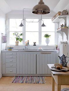 vitt kök med pärlspontsluckor och fönster