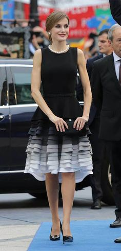 Doña Letizia premiered a bespoke tiered dress from Felipe Varela in black silk cady fabric featuring an asymmetric ruffled skirt and ombre effect. The silhouette is reminiscent of a flamenco dress. Queen Letizia wore a beautiful choker pearl necklace and coordinated with a pair of diamond & pearl earrings. Finally she wore Magrit 'Mila' black patent pointed toe pumps and carried a black satin clutch. Ansorena. Princess of Asturias Awards ceremony, Campoamor Theatre, Oct 23, 2015, Oviedo.