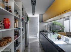 Interligada à sala íntima, a cozinha favorece os momentos de convívio familiar. Note que, sobre a bancada de granito verde ubatuba (Marmonix), painéis de vidro funcionam apenas como anteparo à pia e ao fogão, sem isolar visualmente o espaço. Projeto da arquiteta Helena Karpouzas.