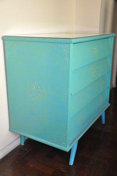 Cômoda que foi restaurada e pintada em azul com nuances em verde, com relevos e pátina dourada.