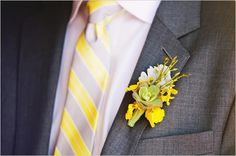 Gray suit, yellow and gray striped tie..