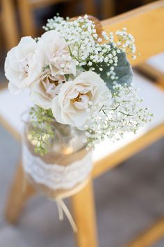 Small arrangements of spray roses, baby's breath and lamb's ear in a burlap and ribbon-wrapped mason jars to line the aisle at a rustic wedding | KLMcelebrations.com