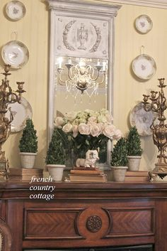 FRENCH COUNTRY COTTAGE: A Fresh Bedroom Mantel - love the plate hangers on middle plates, the mirror (paint job especially) the creamy yellow wall color and wood tones of mantle