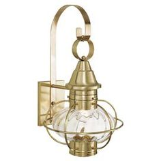 One-light outdoor wall lantern in sienna. Crafted of brass with an oval clear glass shade.
