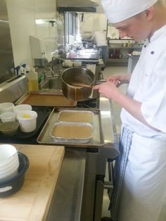 Thomas putting fillung on his base for caramel slice
