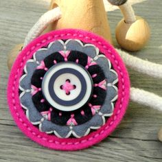 Brooch with felt and embroidery.