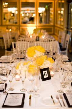 Nice yellow and white centerpieces. Maybe with dark grey table cloths and other color runners.