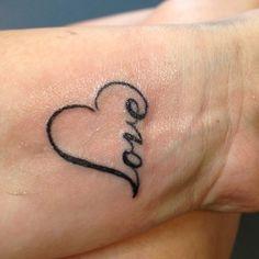 """Pequeño tatuaje en la muñeca que dice """"love""""(amor) en forma de corazón."""