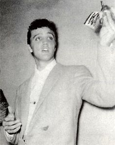 Elvis showing someone a gun, I wonder if it's real or a prop