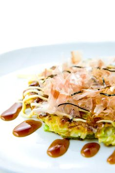 Okonomiyaki | Zen Can Cook - Okonomiyaki is a Japanese style pancake made with chopped cabbage, green onion, batter and various toppings and sauces and like many of the world's greatest everyday foods it doesn't sound like much. The truth is: it's remarkable. I don't speak Japanese but I read somewhere the word 'okonomiyaki' translates into two words: okonomi, which means 'as you like', and yaki, which means 'grilled'.