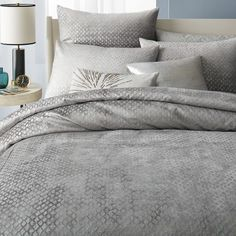 If you like Restoration Hardware, West Elm may have some things you like as well. This bedding set is GORGEOUS and hotel ready because of its subtle metallic texture. Reflected light will make your bed more airy and any neutral pillow with a texture will complement this.