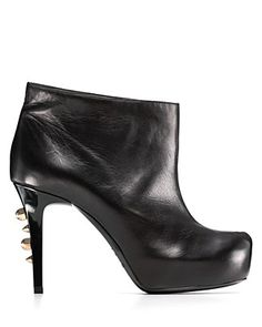 Fierce spikes line the slim heels of these platform leather ankle boots for sharp, industrial chic.