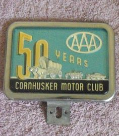 License plate badge from Cornhusker Motor Club, now known as AAA Nebraska.