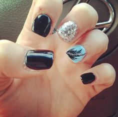 Black acrylic nails with blue feather and silver sparkle accent nails