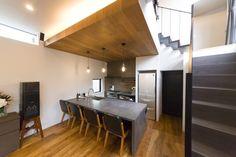 さまざまな素材が見事に融合し、洗練された空間に。キッチン側は一段下げ、座っている人との視線の高さを意識した。「ホームパーティのとき、キッチンに立ちながら一緒に飲めるというアイランドにこだわりました」(絵美香さん) Home Goods, Conference Room, Kitchen, Table, House, Life, Furniture, Home Decor, Cooking
