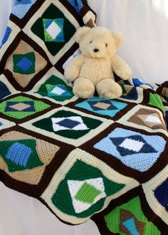 Quilt-style afghan crochet blanket large earth colors big scrap yarn throw blue green brown white diamonds bed coverlet home decor. $300.00, via Etsy.