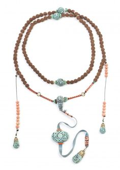 A Chinese Court Necklace,  comprised of 108 sandalwood beads each with pierce carved decoration, 19 carved coral beads, 4 large turquoise colored beads and plaque with a teardrop form pendant at the bottom, with sections of woven silk and having clusters of seed pearls throughout.  Length overall 44 1/4 in