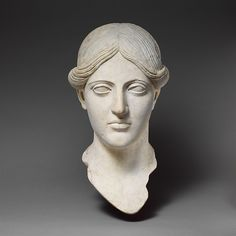 Roman copy of a Greek bronze statue with a fine oval face, sharply defined features and beautifully designed hair, slightly different on the two sides.