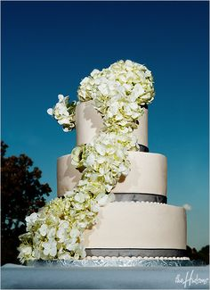 White cake with a waterfall of hydrangea - Photo by Jason