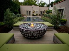 Gabion bowl used for fire pit, and benches set at water level of raised infinity pool...