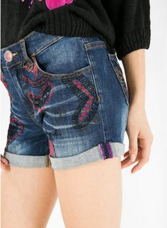 Denim shorts with surprising details like the embroidered patterns and the red button.