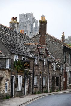 CORFE, DORSET - A street in Corfe with the ruins of Corfe Castle (founded in 11th Century) in the suitably murky background. The castle was deliberately destroyed 360 years ago during the English Civil Way.  (Flickr - Photo Sharing)