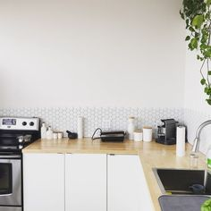 Sparsely decorated kitchen with wooden counter, oven, plant, and tiled backsplash