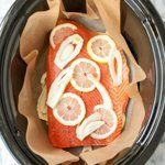 Place one layer of salmon in the slow cooker, skin down. Top with more slices of lemon and aromatics, if using.