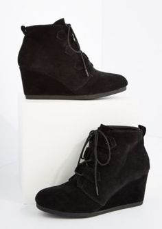 Treat the streets like your personal runway in these stylish lace-up wedged booties! Crafted with black faux suede, white stitching detailing, and front lacing.